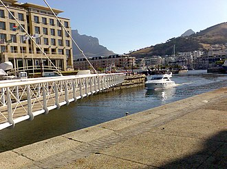Swing bridge - An example of how small swing bridges like this one may be pivoted only at one end, but that does require substantial underground structure to support the pivot. Victoria & Alfred Waterfront, Cape Town.