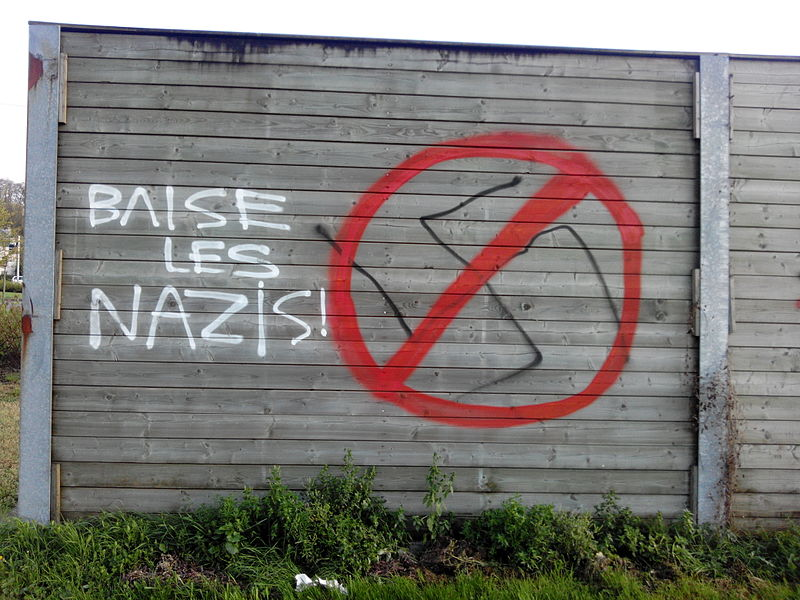 "Wooden noise barriers with tags at Châtelet, Belgium. Dialog between neonazis and antifascists. A hakenkreuz was first tagged on the wall, with other symbols like ACAB. Then, an antifascist edit to the tag has been done to strike the straviska and add a « Baise les nazis » (French for ""Fuck the nazis"")"