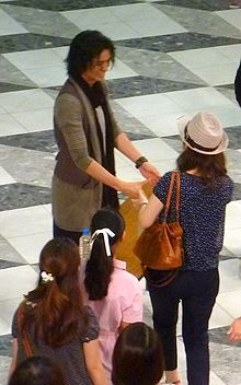 Takumi Saito shakes hands with a row of women, his fans.