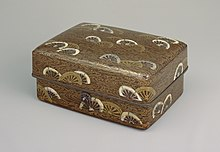 Box with design of wheels in gold and white on black background all over.
