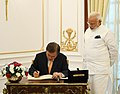 The President of the Republic of South Korea, Mr. Moon Jae-in signing the visitors' book, at Hyderabad House, in New Delhi on July 10, 2018. The Prime Minister, Shri Narendra Modi is also seen.JPG