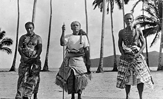 Fa'amatai - Three matai, the two older men bearing the symbols of orator chief status – the fue (flywhisk made of organic sennit rope with a wooden handle) over their left shoulder. The central elder holds the orator's wooden staff (to'oto'o) of office and wears an 'ie toga, fine matting. The other two men wear tapa cloth with patterned designs.
