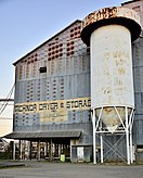 "Photo of a rusted structure built of corrugated sheet metal, painted with faded letters reading ""Tichnor Dryer & Storage"", sitting just behind a tall, cylindrical rice storage elevator."