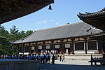 Wooden building with white walls and a hip-and-gable roof built on a stone platform.