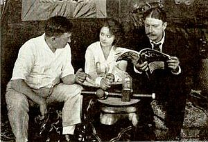 Motion Picture News - Director Perry N. Vekroff and actors Frankie Mann and Stuart Holmes the during production of Trailed by Three (1920), shown reading the Motion Picture News