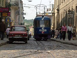 A Lviv tram on a small cobblestone sidestreet in the Old Town.