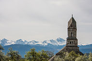 The tower of a church and snowy mountains in the distance