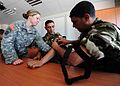 U.S. Army Staff Sgt. Catie Cejka, left, with the 396th Combat Support Hospital, helps Algerian People's National Army Master Sgt. Larbi Essaidi Kamel, center, and Master Sgt. Abdelkader Chetitah as they practice 120514-N-QD416-114.jpg