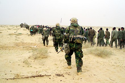 US Marines escort captured enemy prisoners to a holding area in the desert of Iraq on 21 March 2003. U.S. Marines with Iraqi POWs - March 21, 2003.jpg