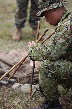Weapon mount - A Japanese soldier examines a rifle tripod during training with US Marines