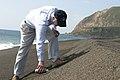 US Navy 040227-M-7842H-007 Gordon R. England, Secretary of the Navy, collects a sample of sand as a souvenir on a beach on the island of Iwo Jima.jpg