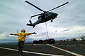 US Navy 050408-N-0357S-026 A Landing Signal Enlisted Sailor guides an MH-60S Seahawk helicopter, assigned to Helicopter Combat Support Squadron Five (HC-5), during a vertical replenishment aboard the Military Sealift Command (.jpg