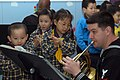 US Navy 070205-N-9604C-193 Musician 2nd Class Bob Booker assigned to 7th Fleet Navy Band, plays the horn for a group of nursery school children at the Society for Protection of Children, Hok Sam House.jpg