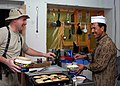 US Navy 071030-N-7415V-003 Culinary Specialist 2nd Timothy Wright, assigned to the Combined Security Transition Command-Afghanistan, teaches Nasim, the Afghan cook, how to make an apple dessert.jpg