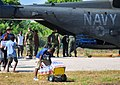 US Navy 100120-N-4774B-380 Haitian citizens and members of the Canadian military help the crew of an MH-53E Sea Dragon helicopter unload food packages and water in Jacmel, Haiti.jpg