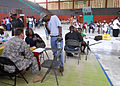 US Navy 100208-N-6214F-030 An Army Special Forces medic interviews a Haitian patient at an improvised clinic operated by the Crudem Foundation in a community gymnasium.jpg