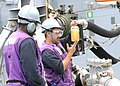 US Navy 100209-N-7088A-104 Gas Turbine Systems Technician (Mechanical) 2nd Class Jose Ramos inspects fuel while Gas Turbine Systems Technician (Mechanical) 3rd Class Maurice Williams observes during an underway replenishment.jpg
