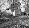 foto van Bakstenen woonhuis met klokgevel met zware rollaag onder zadeldak, aan de achterzijde met wolfeind; aan de voorzijde tegen een gevel met ingezwenkte zijkanten