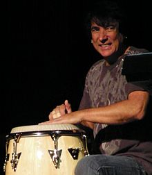 Photo of Walfredo Reyes Jr. smiling and playing a conga drum, at a live Chicago concert in 2013