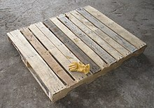 The classic wooden pallet, with a glove for scale.