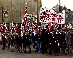 Photograph of people carrying Union Flags, demonstrating outside a factory.