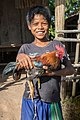 Young boy smiling, holding a fighting rooster in Laos.jpg