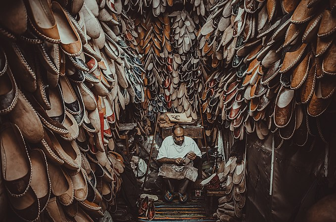 Photograph of Jamal sitting and crafting a shoe in a small room whose walls are covered with hundreds of shoes
