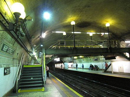 Yellow platform edges, yellow staircase steps and yellow railings, painted for safety, at the IRT Broadway-Seventh Avenue Line platform at 168th Street 168th Street IRT Broadway 2.JPG