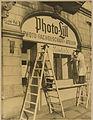 1946-07 Lister Platz Ecke Jakobistraße 1 in Hannover, Werbe-Schrftzug-Bemalung am Schaufenster von Photo-Lill, Foto-Fachgeschäft, Atelier, Kodak, Männer mit Hut auf Leiter-Gerüst.jpg