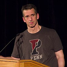 "A 47-year-old white man is standing behing a lectern, looking to the camera's right; he has dark hair, and is wearing a grey t-shirt that says ""PENN"""