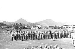 A group of Marines standing at attention on a basketball court, with Hawaiian mountains in the background.