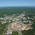 Gelände des Brookhaven National Laboratory 2010: Im Vordergrund die damals im Bau befindliche National Synchrotron Light Source II, rechts oben der Relativistic Heavy Ion Collider, dazwischen mehrere abgeschaltete Forschungseinrichtungen wie der Brookhaven Graphite Research Reactor und der High Flux Beam Reactor