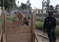 An Iraqi police officer with the major terrorism K-9 unit guides his dog through an obstacle course during training at Contingency Operating Site Diamondback, in Mosul, Ninevah province, Iraq, May 23, 2011 110523-A-RH393-061.jpg
