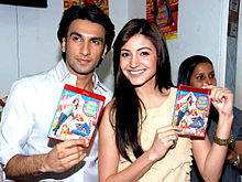 Anushka Sharma and Ranveer Singh holding up DVDs. While Sharma, wearing a pale yellow top is smiling directly at the camera, Singh, dressed in a white shirt, is looking away.