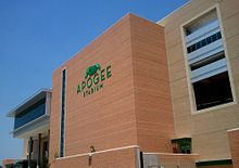 "A large, contemporary structure with a light green logo that says ""Apogee Stadium""."