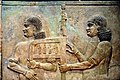 Assyrian eunuchs carrying Sargon II's throne.jpg