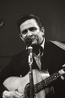 Cash singing into a microphone and strumming a guitar