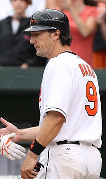 "A man in a white baseball uniform faces to the left. He reaches to shake hands with another unseen person. His uniform reads ""Bako"" in small orange print and ""9"" in larger orange print on the back, and he is wearing a black batting helmet with an orange-and-black bird on the face."