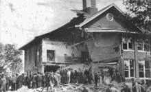 onlookers mill around, looking at the half-destroyed Bath School building