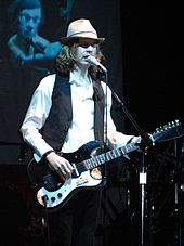 Beck playing the guitar during a concert.