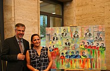 """Train of Instances, 2013, oil on canvas, 120 × 87 cm: Serap Riedel with the President of the Federal Social Court, Peter Masuch, at the vernissage of the exhibition """"Train of Instances - An Artistic Confrontation with Law and Justice"""" on July 10, 2014"""