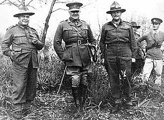 Trois officiers debout posant pour une photograhie, avec deux autres soldats au fond à droite.