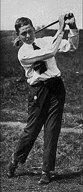 A young man in a white shirt, dark tie and dark pants completing a right-handed golf swing