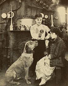 Black and white photo of a young man, a young woman, and a dog