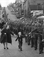 A line of uniformed soldiers march through town. One reaches towards a young boy running beside the column, pursued by a woman