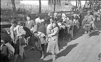 The Holocaust in Russia - Russia. Jewish women and children being forced out of their homes. A Romanian soldier is marching along as a guard, 17 July 1941