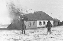 Two Waffen-SS look at a burning farmer's house near Kharkov, February 1943