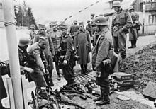 A black and white photograph of German soldiers watching other soldiers laying down their rifles in a pile