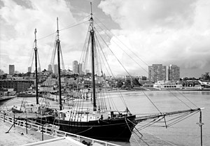 A sailing ship at a pier, starboard bow quarter view