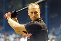 "A man with short hair prepares to swing a baseball bat. He is wearing a black shirt with ""Orioles"" written in orange (obscured), and the bat is held over his right shoulder. He is wearing orange and black batting gloves on his hands."